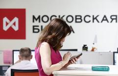 A woman uses a smart phone on the floor of the Moscow Exchange June 3, 2014. Russia's largest lenders, Sberbank and VTB, are likely to lead a decline in Moscow shares on August 1, 2014, after being hit by sanctions, with a slump in U.S. markets on global economy concerns and tensions with Russia also weighing. Picture taken June 3, 2014. REUTERS/Sergei Karpukhin (RUSSIA - Tags: BUSINESS POLITICS)