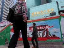 Passers-by walk on a footbridge in front of the Shenzhen Stock Exchange, China January 5, 2011. REUTERS/Bobby Yip/ File Photo