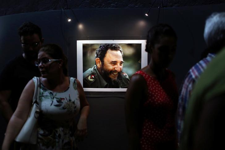 People look at a picture of Cuba's former President Fidel Castro during the opening of the exhibition ''Fidel'' in Havana, Cuba, August 12, 2016.  REUTERS/Alexandre Meneghini