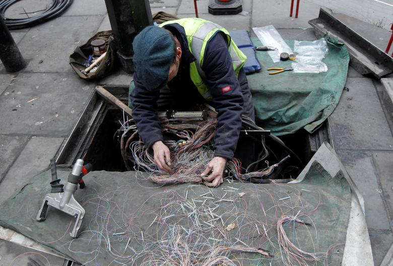 A British Telecom engineer repairs cables to the telephone and internet network in central London, Britain, January 23, 2011.    REUTERS/Luke MacGregor/File Photo