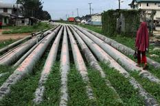 A girl walks on a gas pipeline running through Okrika community near Nigeria's oil hub city of Port Harcourt December 4, 2012.  REUTERS/Akintunde Akinleye/File Photo