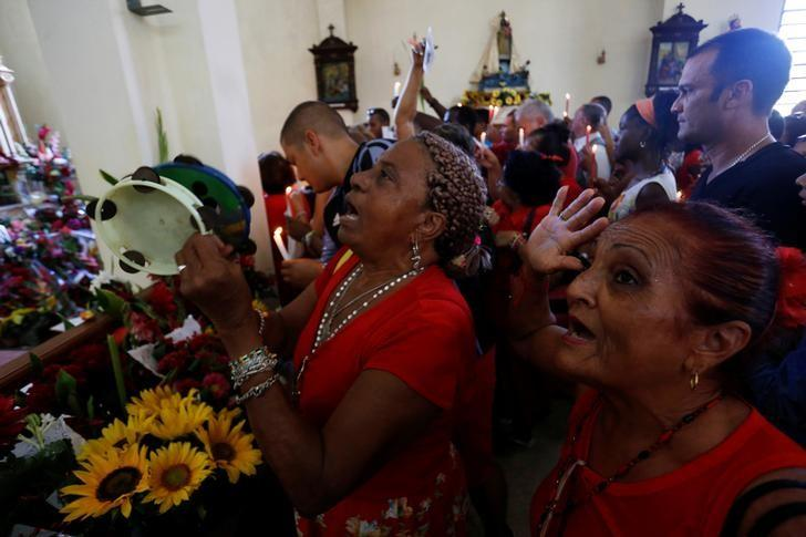 People gather at the Saint Barbara Church to pray on the day known as Santa Barbara to Catholics and Chango to followers of Cuba's Santeria religion, in Havana, Cuba, December 4, 2016. REUTERS/Stringer