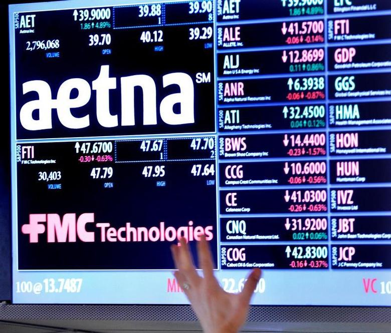 A trader points up at a display on the floor of the New York Stock Exchange August 20, 2012.  REUTERS/Brendan McDermid/File Photo