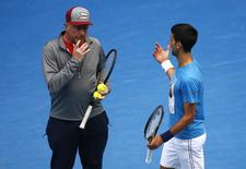 Serbia's Novak Djokovic talks with his coach Boris Becker during a practice session on the eve of his final match against Britain's Andy Murray, at the Australian Open tennis tournament at Melbourne Park, Australia, January 30, 2016. REUTERS/Jason Reed