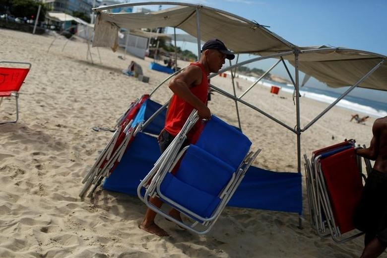A man carries chairs to be rented to visitors at Ipanema beach in Rio de Janeiro April 29, 2014. REUTERS/Pilar Olivares/File Photo