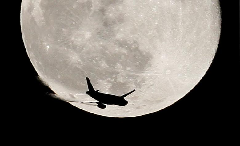 An airplane is silhouetted against a full moon in the sky over London in this January 1, 2010 file photo. REUTERS/Suzanne Plunkett