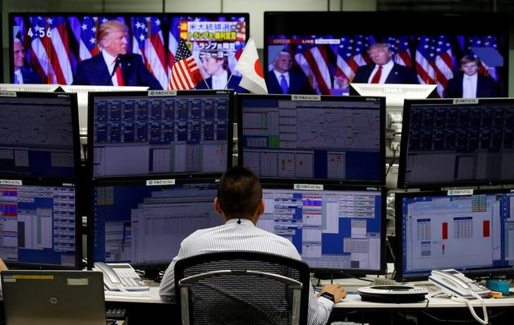 An employee of a foreign exchange trading company works near monitors showing U.S. President-elect Donald Trump speaking on TV (top) in Tokyo, Japan, November 9, 2016.   REUTERS/Toru Hanai/Files