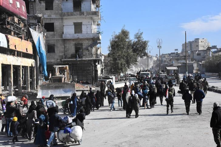People, who left the eastern districts of Aleppo, carry their belongings as they walk in a government held area of Aleppo, Syria, in this handout picture provided by SANA on December 8, 2016. SANA/Handout via REUTERS