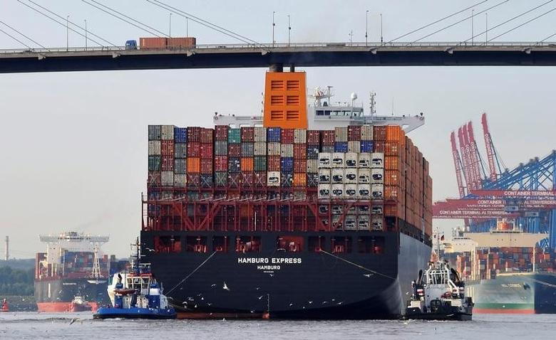 Towboats tow the container ship ''Hamburg Express'' as it passes below the Koehlbrand bridge during its arrival near the Port of Hamburg, August 15, 2012.     REUTERS/Morris Mac Matzen/File Photo