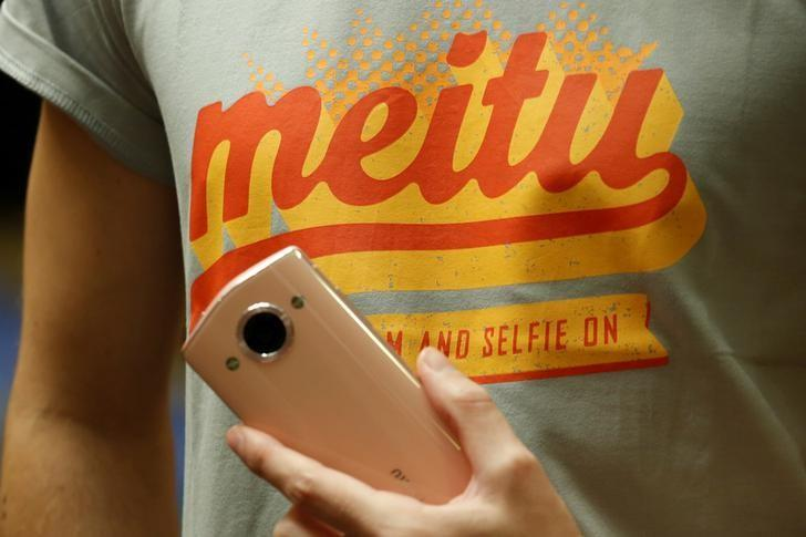 A model poses with a Meitu smartphone during Meitu IPO news conference in Hong Kong, China December 2, 2016.  REUTERS/Bobby Yip