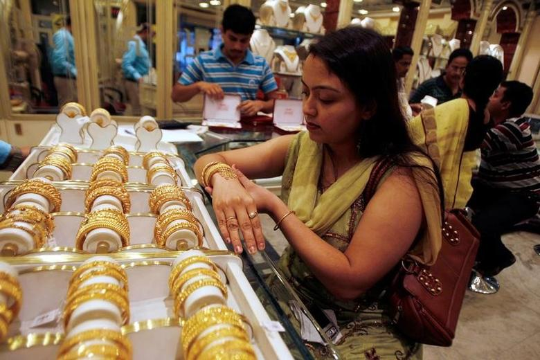 A woman tries on a gold bracelet at a jewellery showroom in the eastern Indian city of Siliguri November 4, 2009.  REUTERS/Rupak De Chowdhuri/File Photo