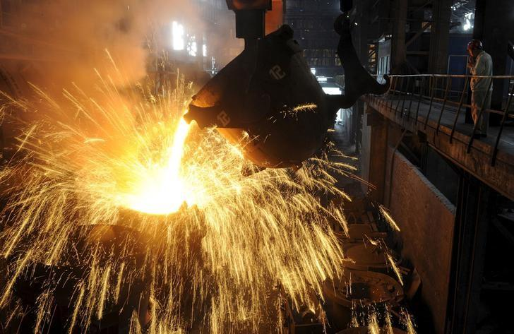 An employee monitors molten iron being poured into a container at a steel plant in Hefei, Anhui province September 9, 2013.  REUTERS/Stringer/File Photo