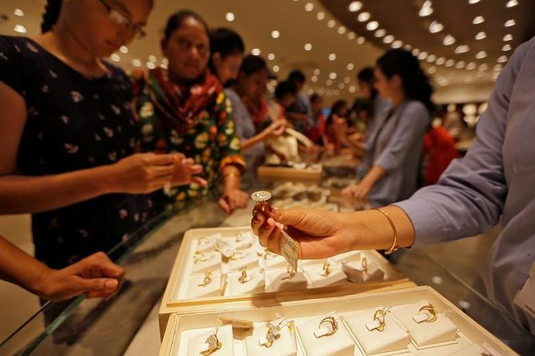 A sales person shows a gold ring to customers at a jewellery showroom during Dhanteras, a Hindu festival associated with Lakshmi, the goddess of wealth, in Ahmedabad, India, October 28, 2016. REUTERS/Amit Dave