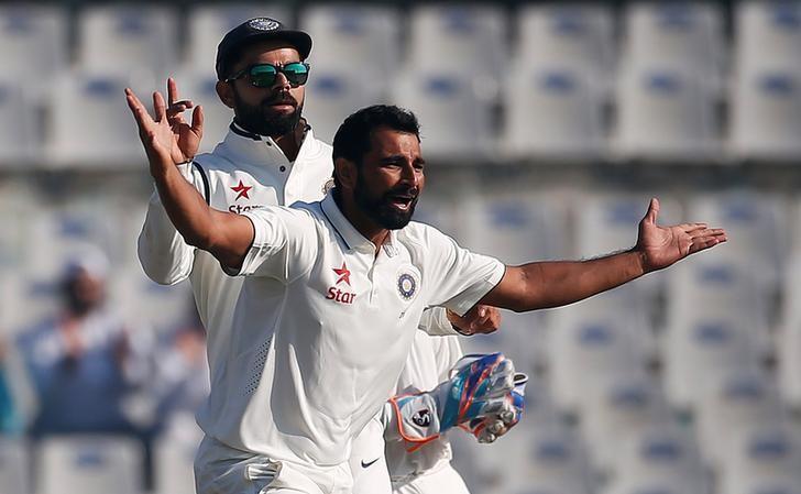 Cricket - India v England - Third Test cricket match - Punjab Cricket Association Stadium, Mohali, India - 27/11/16. India's Mohammed Shami and Virat Kohli (L) celebrate the dismissal of England's Adil Rashid. REUTERS/Adnan Abidi