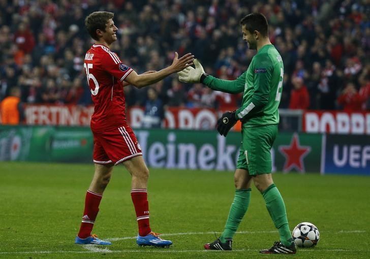 Arsenal's Lukasz Fabianski (R) goes for a handshake with Bayern Munich's Thomas Mueller after their Champions League round of 16 second leg soccer match in Munich, March 11, 2014.  REUTERS/Kai Pfaffenbach/File Photo