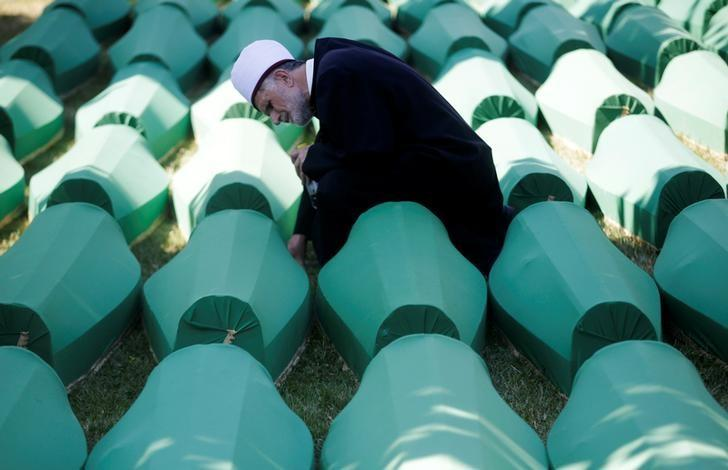 Muslim effendi sits near coffins of his relatives, who are newly identified victims of the 1995 Srebrenica massacre, which are lined up for a joint burial in Potocari near Srebrenica, Bosnia and Herzegovina July 11, 2016. REUTERS/Dado Ruvic/Files