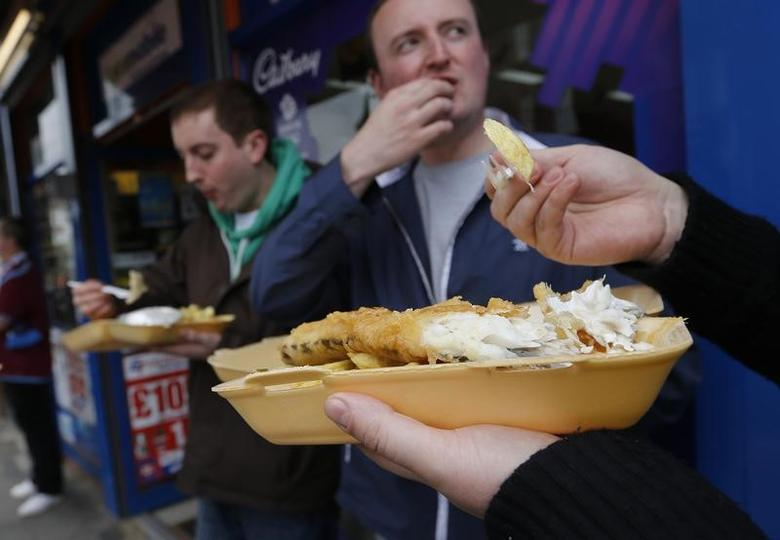Customers eat their takeaway fish and chips outside the Wembley Bay fish and chip shop in west London May 13, 2012.  REUTERS/Eddie Keogh