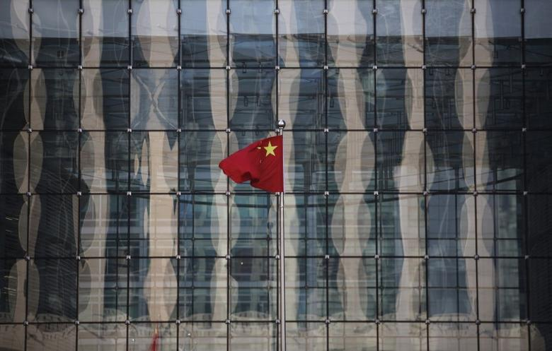 A Chinese national flag flutters at the headquarters of a commercial bank on a financial street near the headquarters of the People's Bank of China, China's central bank, in central Beijing November 24, 2014. REUTERS/Kim Kyung-Hoon/Files