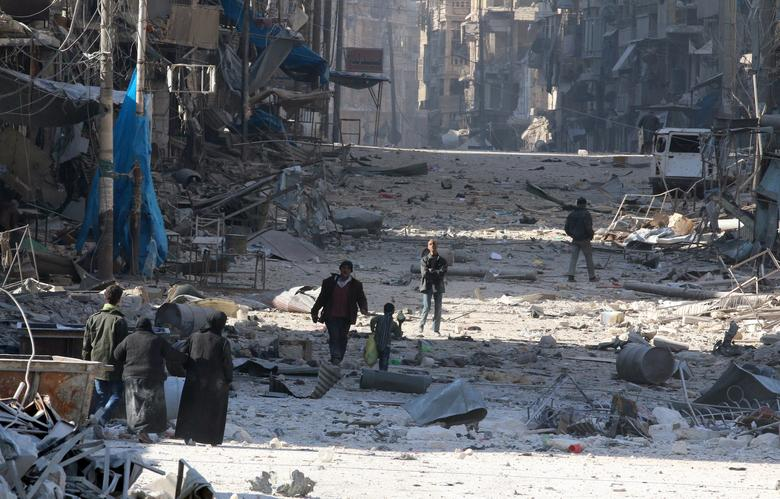 Syrians walk over rubble of damaged buildings, while carrying their belongings, as they flee clashes between government forces and rebels in Tariq al-Bab and al-Sakhour neighborhoods of eastern Aleppo towards other rebel held besieged areas of Aleppo, Syria November 28, 2016. REUTERS/Abdalrhman Ismail