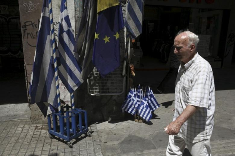 A man walks past Greek national flags and European Union flags on display outside a shop in central Athens, Greece July 24, 2015. REUTERS/Yiannis Kourtoglou