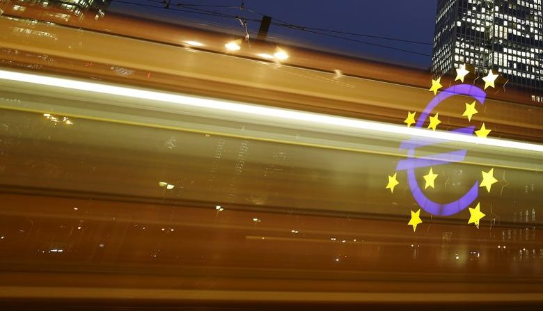 The famous euro sign landmark is seen through the lights of a passing tram outside the former headquarters of the European Central Bank (ECB) in Frankfurt, Germany, January 19, 2016.    REUTERS/Kai Pfaffenbach