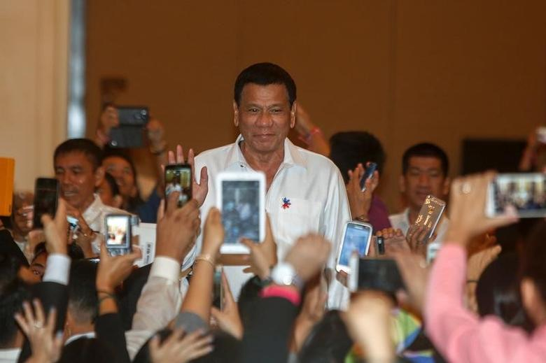 Philippine President Rodrigo Duterte greets people before a meeting with the Filipino Community at a hotel in Phnom Penh, December 13, 2016. REUTERS/Samrang Pring