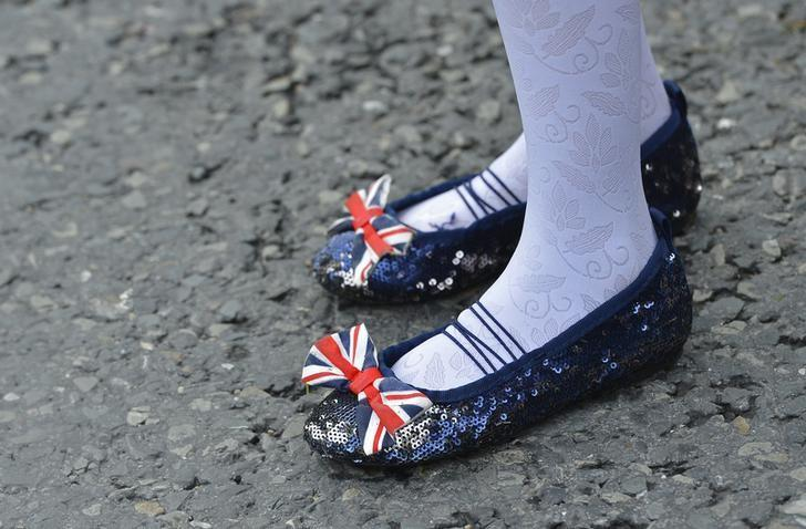 A young spectator wears patriotically themed clothing as she watches the Olympic Torch Relay in Plymouth, south west England May 20, 2012. REUTERS/Toby Melville/Files