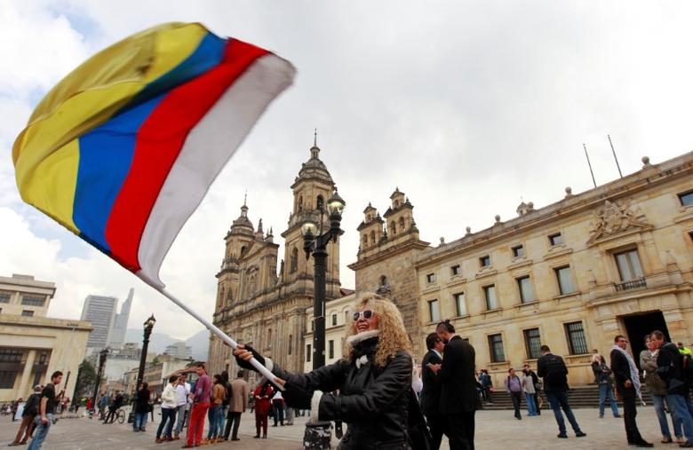 People demonstrate on the street as Colombia's President Juan Manuel Santos and Marxist FARC rebel leader Rodrigo Londono, known as Timochenko, sign a new peace accord in Bogota, Colombia November 24, 2016.  REUTERS/Felipe Caicedo