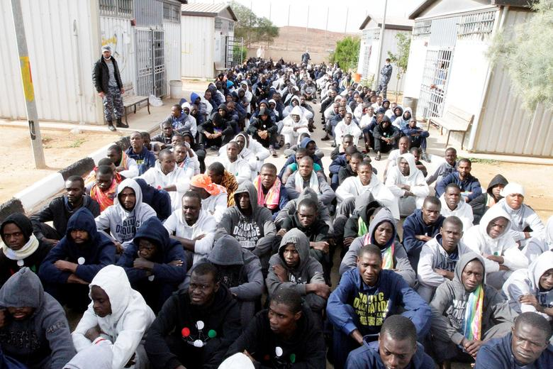 Illegal migrants, who have been detained after trying to get to Europe, sit in row on the ground of a detention camp in Gheryan, outside Tripoli, Libya December 1, 2016. REUTERS/Hani Amara