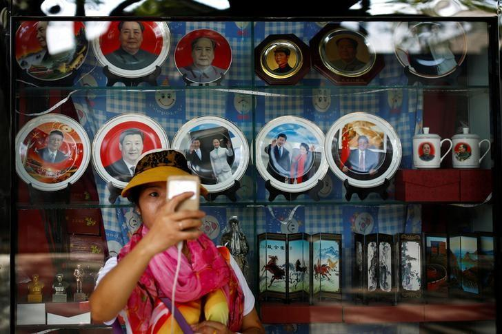 A woman takes a selfie in front of souvenirs featuring portraits of China's late Chairman Mao Zedong and China's President Xi Jinping outside a shop near the Forbidden City in Beijing, China, September 9, 2016. REUTERS/Thomas Peter