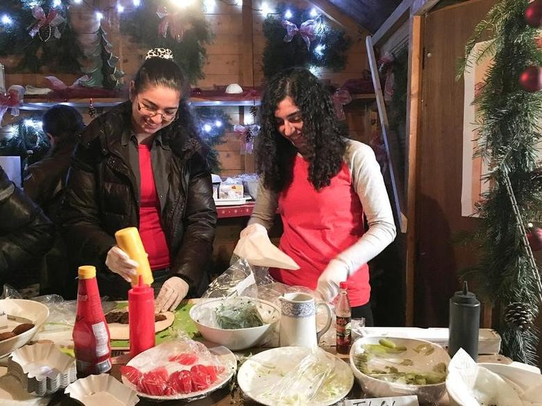Syrian refugees Mayar and Nawar Ballish serve falafel sandwiches at a traditional German Christmas market in the small Bavarian town of Schillingsfuerst, Germany November 11, 2016. REUTERS/Michelle Martin