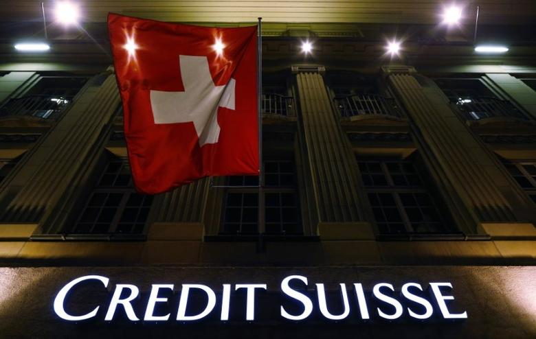 The logo of Swiss bank Credit Suisse is seen below the Swiss national flag at a building in the Federal Square in Bern May 15, 2014. Credit Suisse Group AG is expected to plead guilty and pay more than $2.5 billion to U.S. authorities to resolve charges that the Swiss bank helped Americans evade U.S. taxes, people familiar with the discussions said on Thursday.   REUTERS/Ruben Sprich (SWITZERLAND - Tags: BUSINESS LOGO CRIME LAW) - RTR3PDQJ