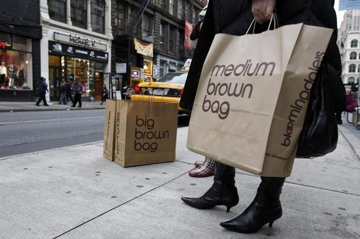 A shopper holds her bags as she tries to hail a cab in New York November 22, 2011. REUTERS/Jessica Rinaldi/Files