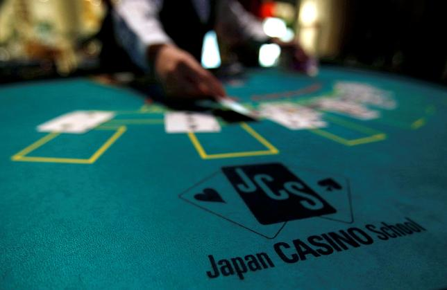 A logo of Japan casino school is seen as a dealer puts cards on a mock black jack casino table during a photo opportunity at an international tourism promotion symposium in Tokyo, Japan September 28, 2013. REUTERS/Yuya Shino/File Photo