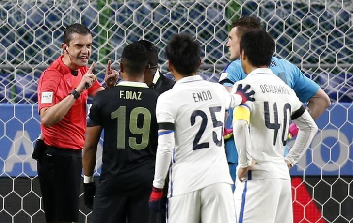 Football Soccer - Atletico Nacional v Kashima Antlers - FIFA Club World Cup Semi Final - Suita City Football Stadium, Osaka, Japan - 14/12/16 Atletico Nacional players remonstrate with Referee Viktor Kassai as he awards a penalty to Kashima Antlers Reuters / Kim Kyung-Hoon Livepic