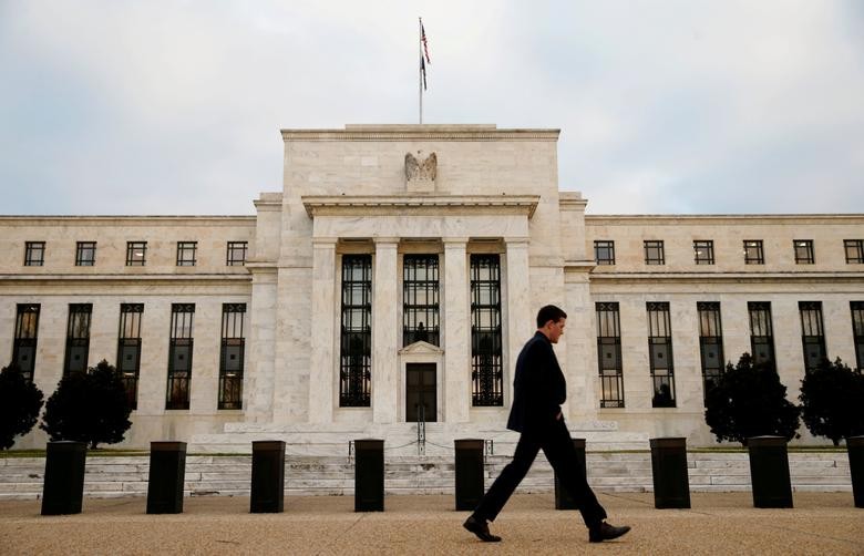 FILE PHOTO: A man walks past the Federal Reserve Bank in Washington, D.C., U.S. December 16, 2015.   REUTERS/Kevin Lamarque/File Photo