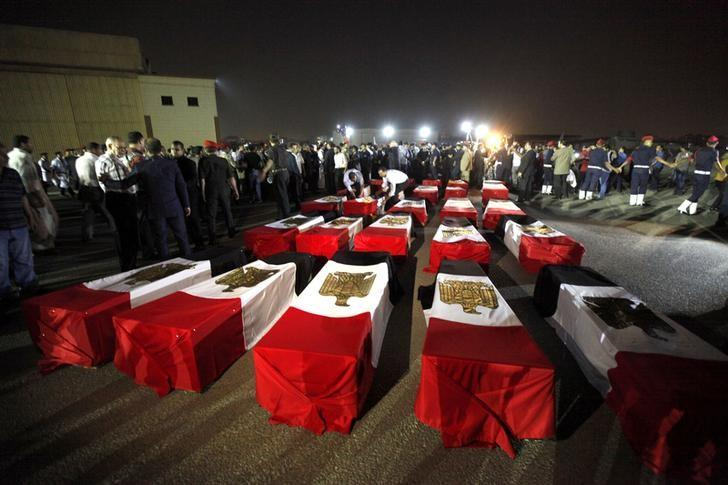 FILE PHOTO - The caskets of 25 policemen killed early Monday morning near the north Sinai town of Rafah lay on the ground after arriving at Almaza military airport in Cairo August 19, 2013. REUTERS/Mohamed Abd El Ghany