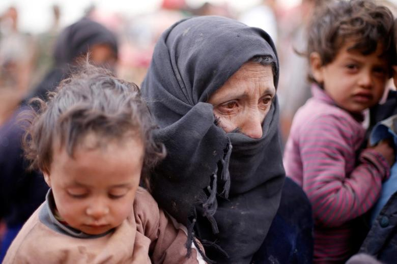 A Syrian refugee, who is stuck in between the Jordanian and Syrian borders, cries and holds her child as she waits to cross into Jordan after a group of refugees had crossed into Jordanian territory, near the town of Ruwaished at the Hadalat area, east of the capital Amman, May 4, 2016. REUTERS/Muhammad Hamed