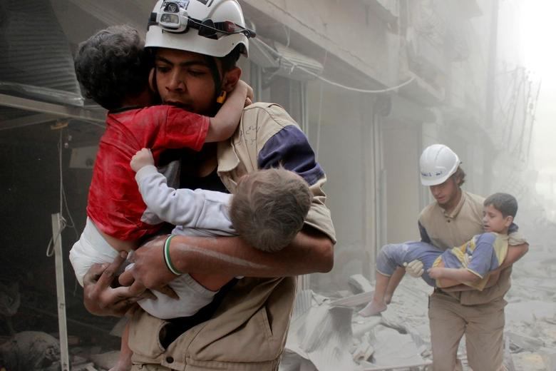Members of the Civil Defence rescue children after what activists said was an air strike by forces loyal to Syria's President Bashar al-Assad in al-Shaar neighbourhood of Aleppo, Syria June 2, 2014. REUTERS/Sultan Kitaz/File Photo