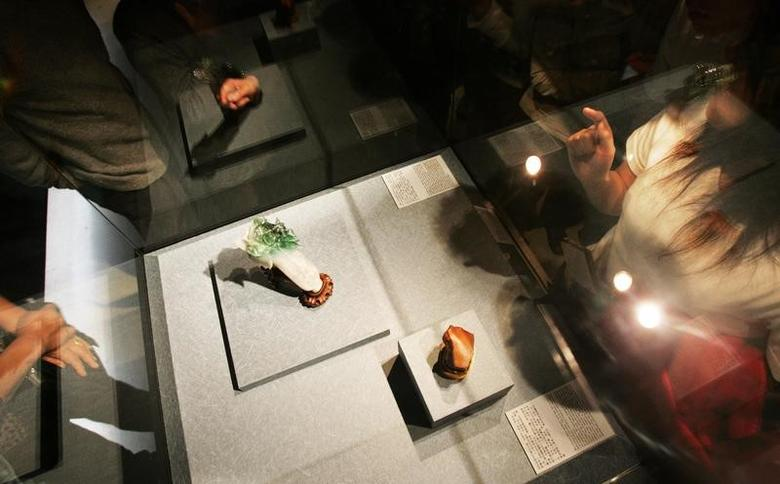Visitors gaze at the Jade Cabbage, one of the most popular exhibits at the National Palace Musem in Taipei, displayed here with a hard rock sculpted like a piece of tender fatty pork January 6, 2005.