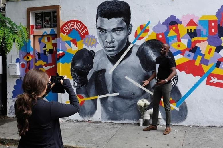 A man has his photograph taken near a makeshift memorial to the late Muhammad Ali in New York, U.S., June 4, 2016.  REUTERS/Lucas Jackson