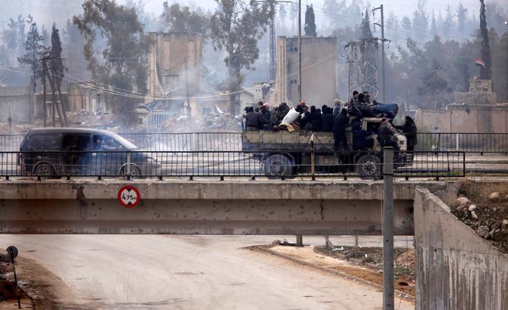 Evacuees from rebel-held eastern Aleppo ride on pick-up trucks along the government-held area of al-Ramousah bridge,  Syria December 16, 2016. REUTERS/Omar Sanadiki