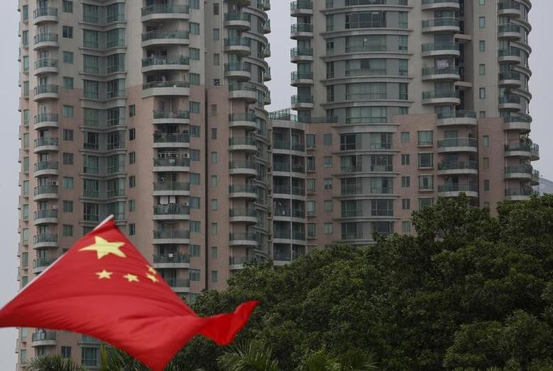 A Chinese national flag flutters in front of an apartment tower in the southern Chinese city of Shenzhen August 28, 2015.  REUTERS/Bobby Yip