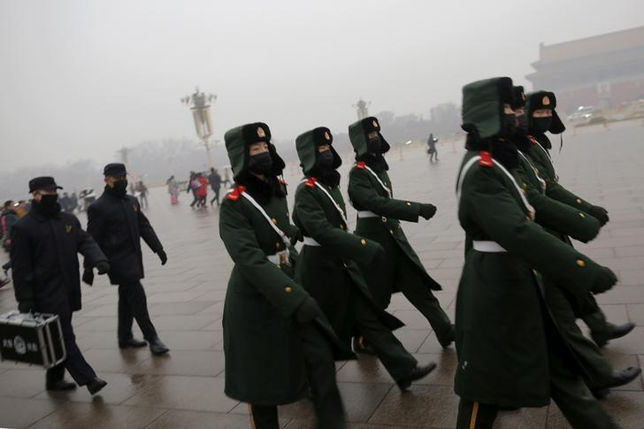 Paramilitary policemen wearing masks march on a cold morning following a flag-raising ceremony amid heavy smog at Tiananmen Square, after the city issued its first ever ''red alert'' for air pollution, in Beijing December 9, 2015.  REUTERS/Damir Sagolj/Files