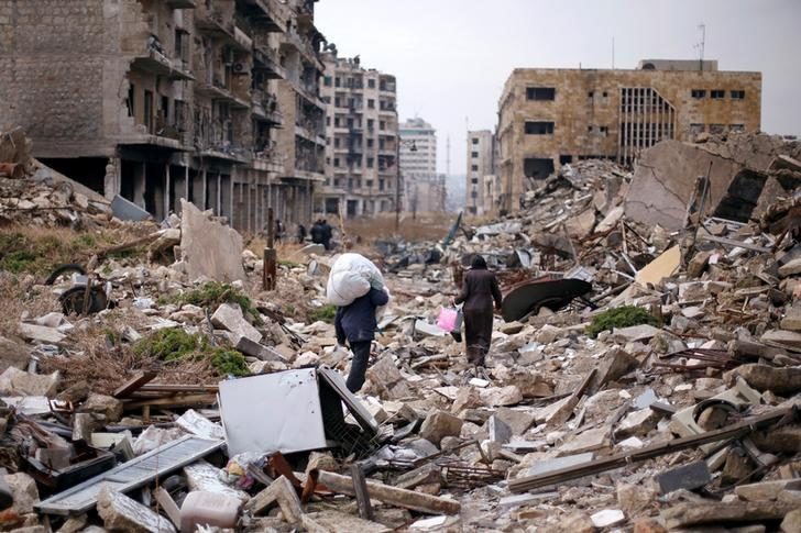 People walk amid the rubble as they carry belongings that they collected from their houses in the government controlled area of Aleppo, Syria December 17, 2016. REUTERS/Omar Sanadiki