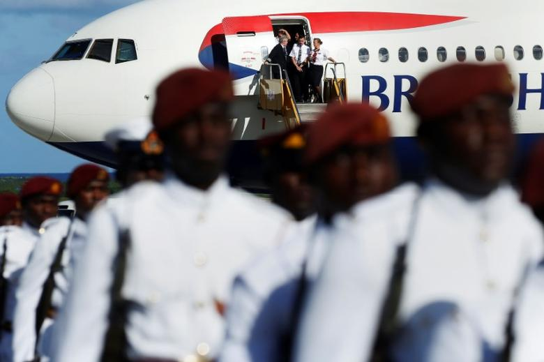 A British Airways flight crew watches as Prince Harry inspects members of Antigua's military as he arrives at the airport for an official visit in Antigua, November 20,  2016.   REUTERS/Carlo Allegri