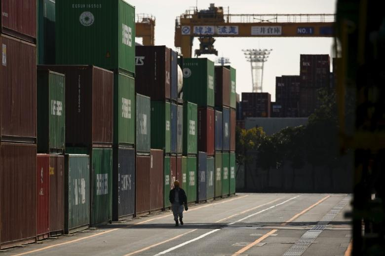 A worker walks between shipping containers at a port in Tokyo, Japan,  February 18, 2016.  REUTERS/Thomas Peter