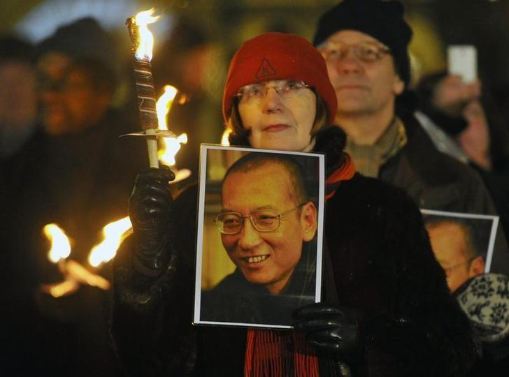 A woman holds a photograph of Liu Xiaobo during a torchlit procession in the centre of Oslo following the Nobel Peace Prize ceremony December 10, 2010.   REUTERS/Toby Melville/Files