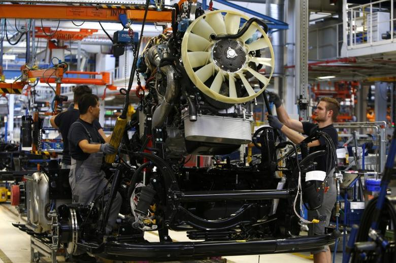 Men work at the assembly line in the truck production plant of truck and bus-maker MAN AG in Munich, Germany July 30, 2015. REUTERS/Michaela Rehle