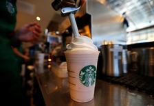FILE PHOTO:  A barista puts whipped cream on a drink at a newly designed Starbucks coffee shop in Fountain Valley, California, U.S. on August 22, 2013.  REUTERS/Mike Blake/File Photo